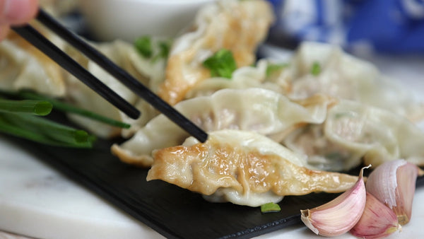 Delicious Sichuan dumplings served with chopsticks, with Grandma's chili sauce