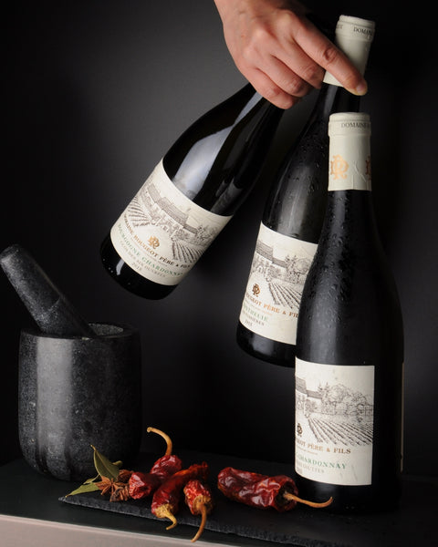 Three bottles of domaine rougeot meursault burgundy french wine, grabbed by hand with chilli and morter