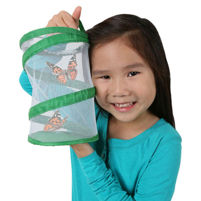 Smiling girl holding up Insect Lore Pop-Up Port-A-Bug. Two orange and black butterflies are fluttering in the small, 8 inch tall, green, pop-up, mesh habitat.
