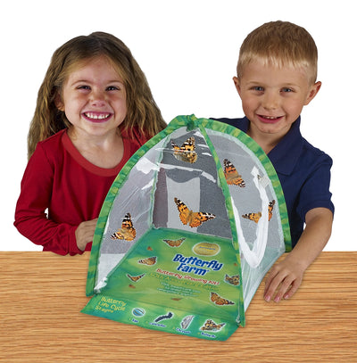 Two children smiling at camera standing behind green, tent-shaped habitat with clear viewing panel, fold-out life cycle learning tool and Painted Lady butterflies fluttering inside.
