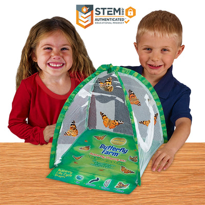 2 happy children with the butterfly farm tent shaped habitat with clear viewing panels and butterflies fluttering inside.