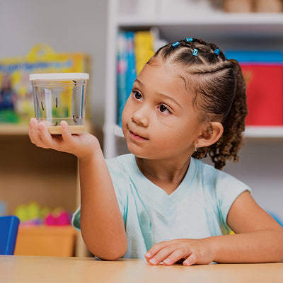 Young smiling girl watching 5 caterpillars eat their brown food in a clear cup with white lid.