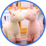 Peluche Licorne rose blanc sur table