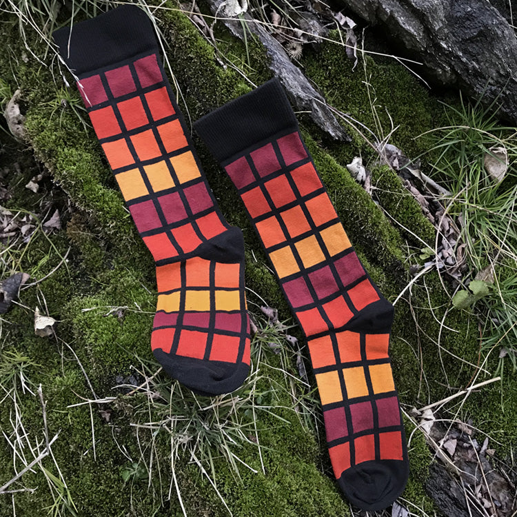 MADE IN USA men's black geometric cotton socks inspired by R62A NYC Subway car with maroon, paprika, orange, + yellow-orange pattern