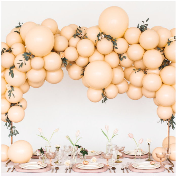 balloons and florals flowers garland arch table setting in peach greenery monochromatic