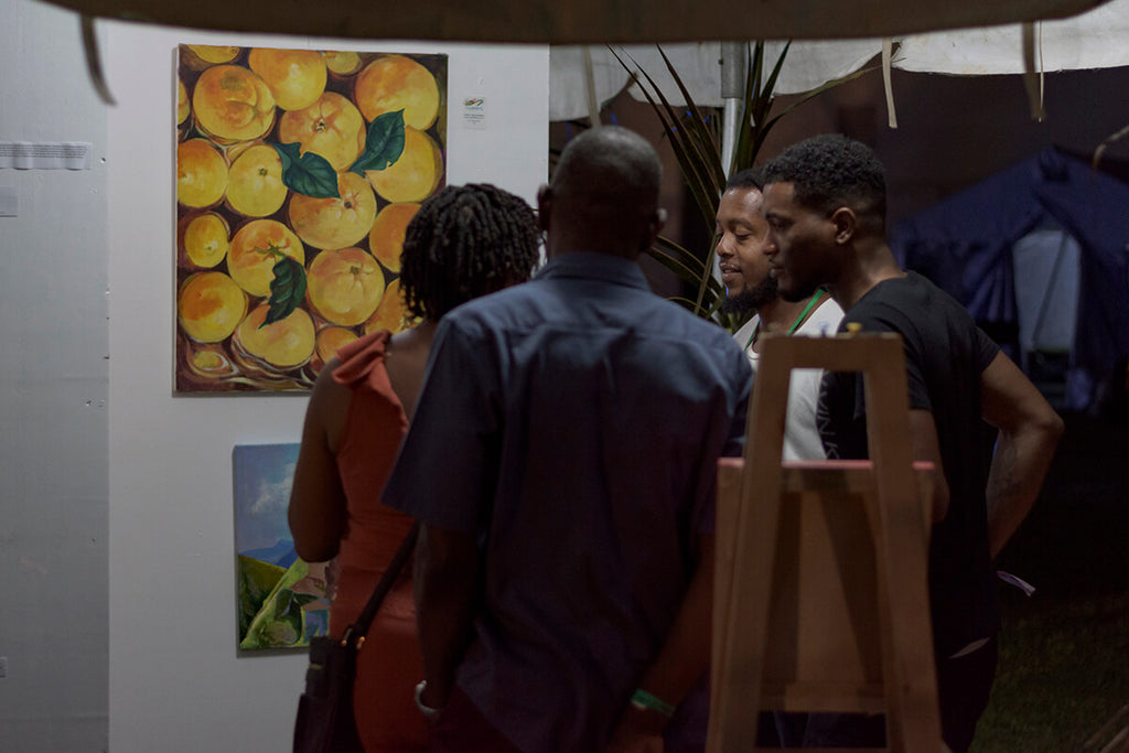 Artist, Shadrach Burton, explaining his art in the Art Gallery section of the VIP area, WCMF, 2019
