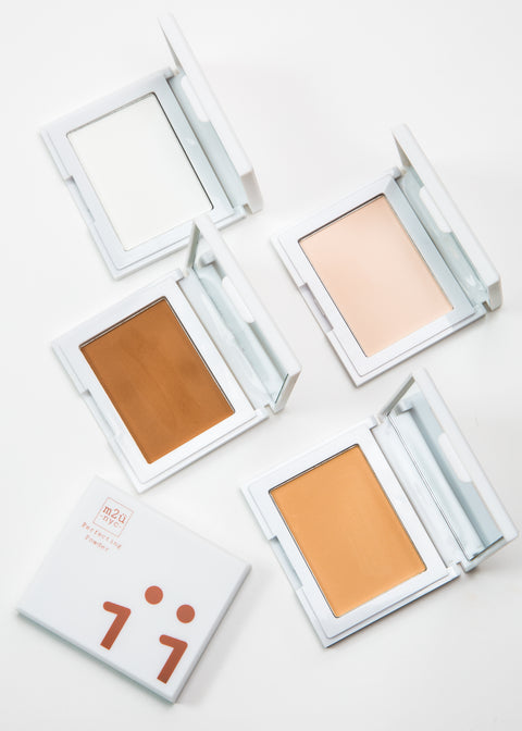 four open perfecting powder compacts in four shades with mirrors and one closed