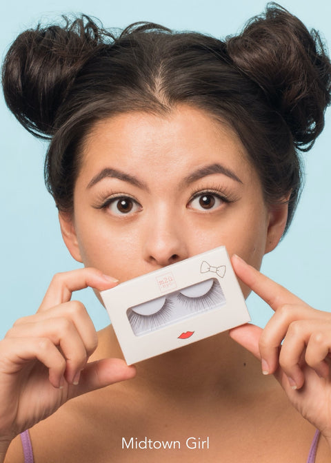girl wearing false eyelashes holding a pair in a white box with red lips