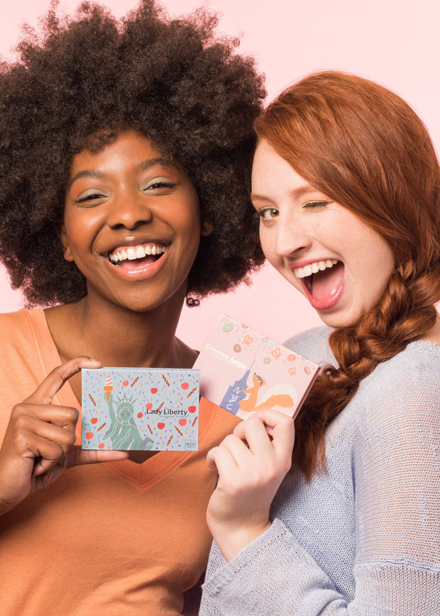 two girls holding different eyeshadow palettes with big smiles and a wink face