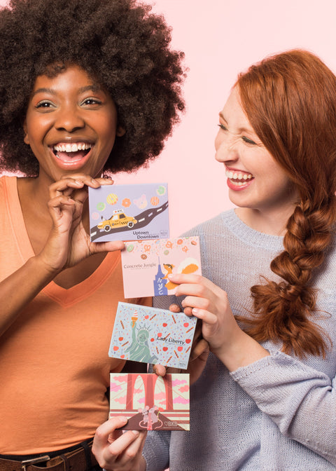 two girls laughing each holding two eyeshadow palettes inspired by new york city