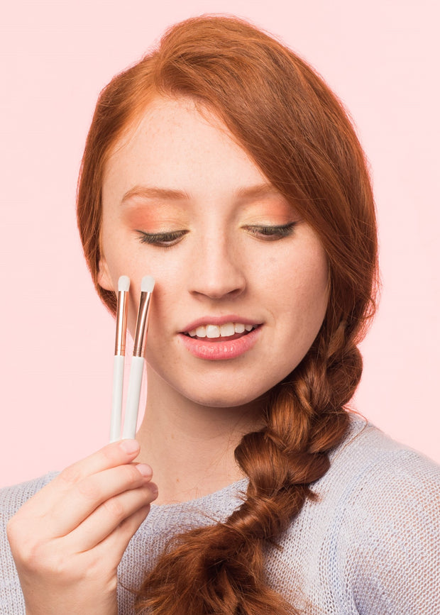 girl wearing eyeshadow looking down holding the eyeshadow brush set