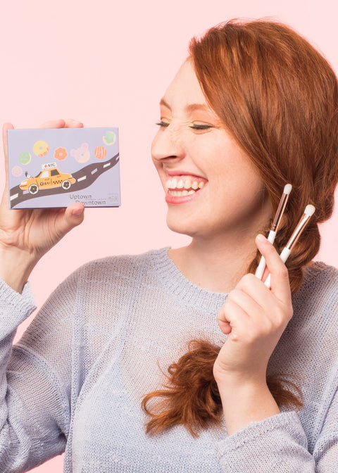 smiling girl holding an eyeshadow palette on one hand and the eyeshadow brush set on the other hand