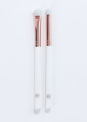 two white and rose gold eyeshadow brushes with different bristle shapes lying next to each other