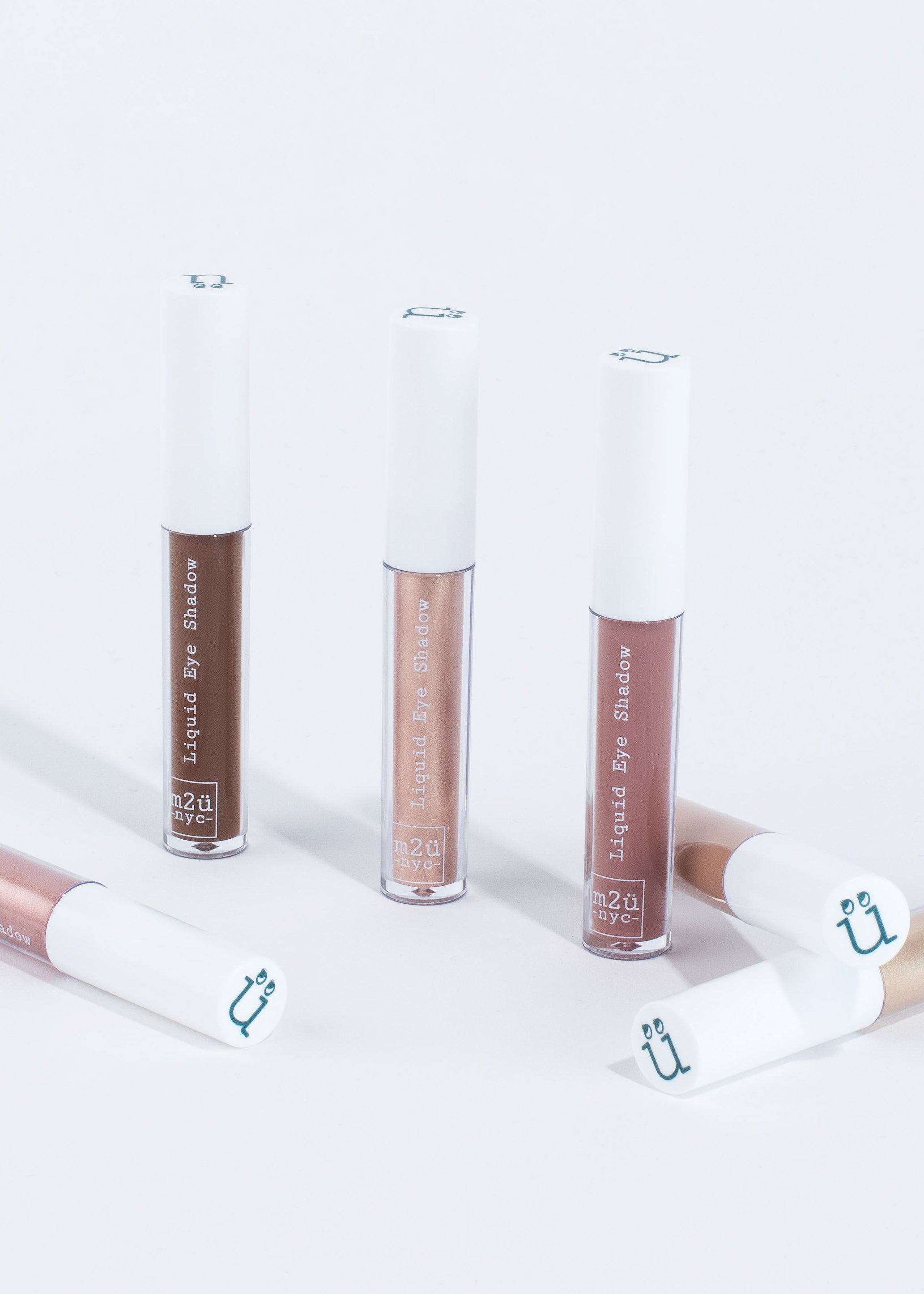 a collection of six liquid eyeshadow in different shades standing and lying down