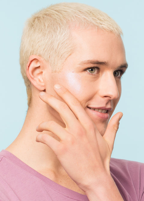 man happily applying jelly highlighter on the right side of his cheek with fingers