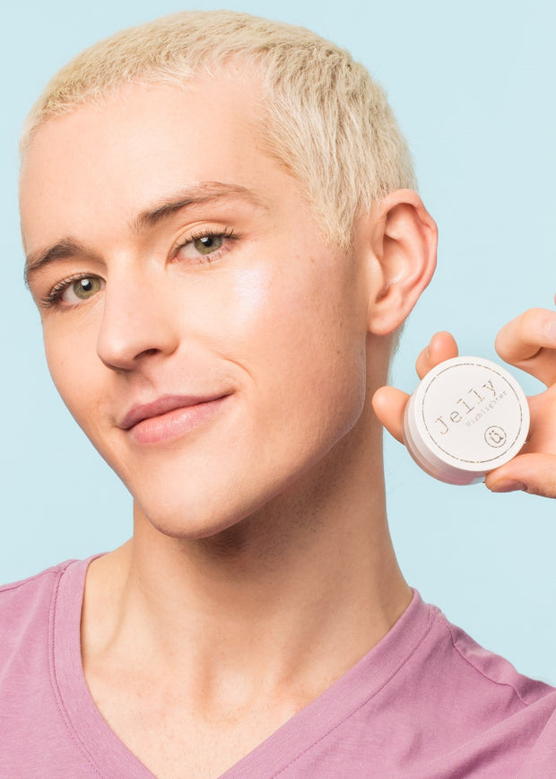 man holding the vegan, cruelty free jelly highlighter with a soft smile