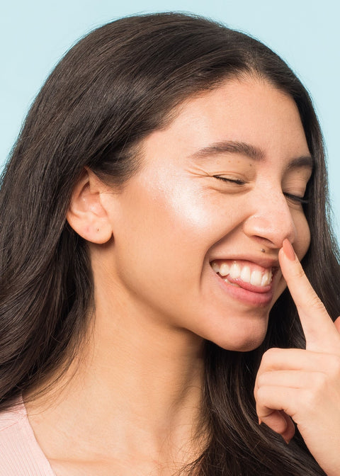 winky smiling girl wearing rose gold liquid highlighter poking her nose