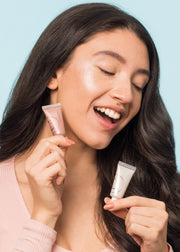 smiling girl looking down holding two tubes of liquid highlighter in two different shades