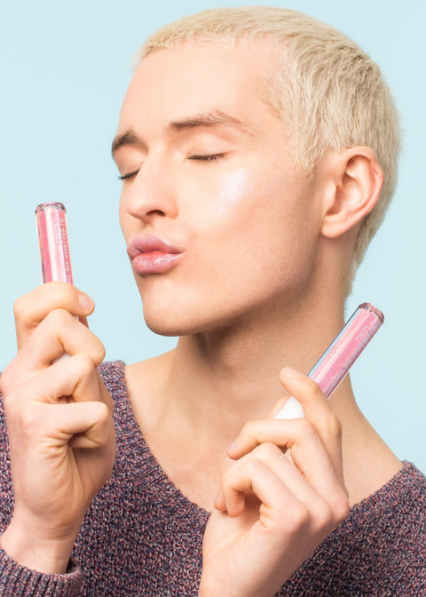 man holding two bottles of the holographic lip gloss air kissing the product with eyes closed