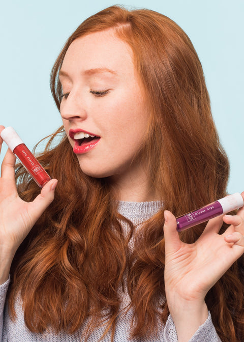 excited girl holding two bottles of lip gloss looking at one of them