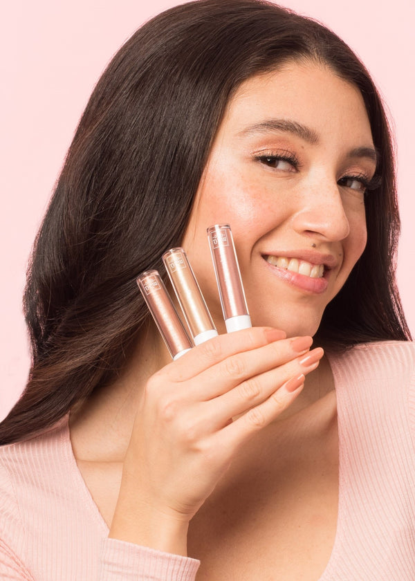 girl wearing eyeshadow holding three bottles of liquid eyeshadow in shade prince, victory and tribeca