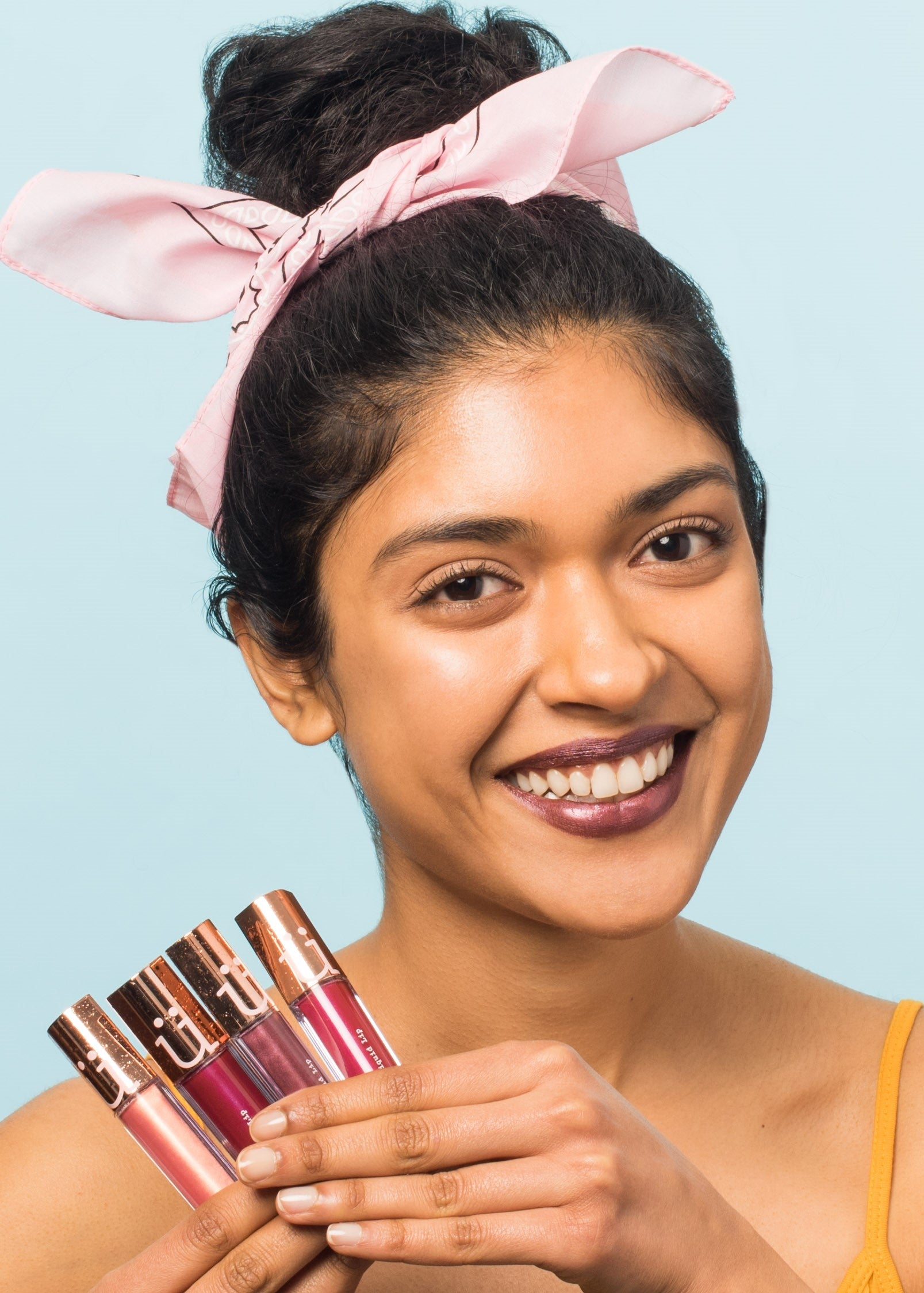 smiling girl wearing metallic liquid lip holding four bottles of metallic liquid lip in different shades