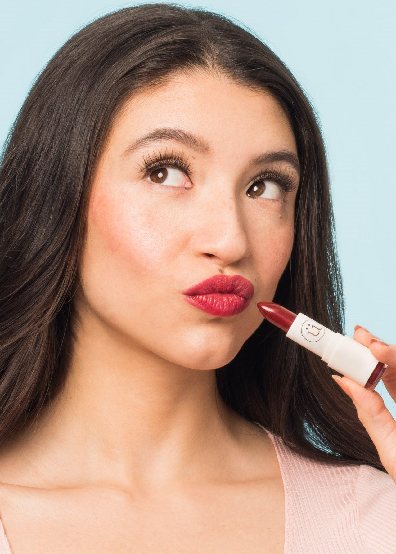 girl looking up pouting her lips holding red moisturizing lipstick toward the lips