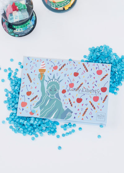 statue of liberty inspired eyeshadow palette sitting among blue sprinkles and two snow globes
