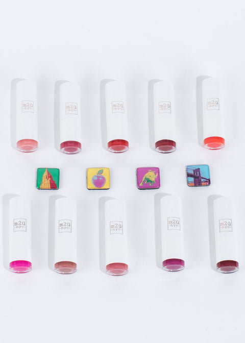 ten moisturizing lipsticks in different shades lying down in two horizontal lines with nyc themed blocks in the middle