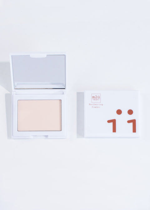 two perfecting powder compacts in shade light, one open and one closed