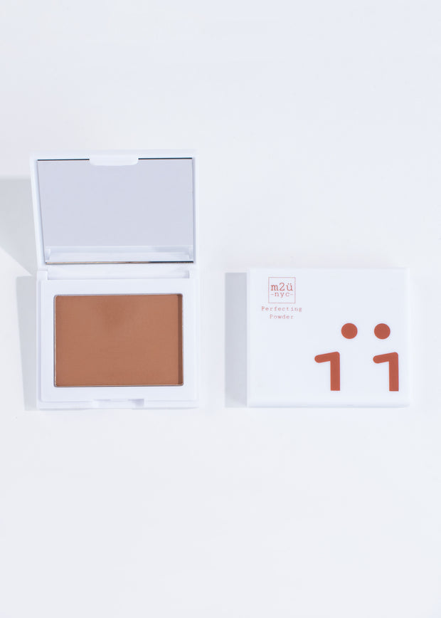 two perfecting powder compacts in shade dark, one open and one closed