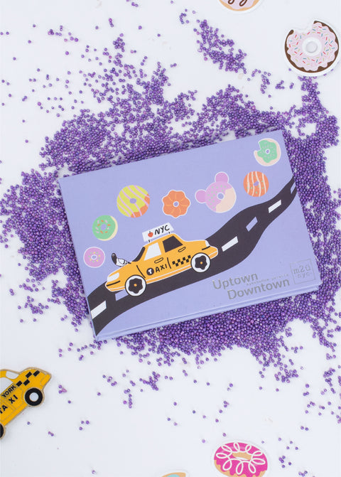 new york city inspired eyeshadow palette sitting among purple sprinkles, donuts and mini taxi