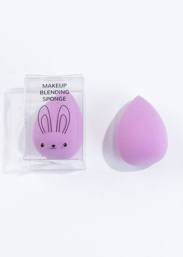 two egg-shaped purple makeup blending sponge, one in a clear box with rabbit illustration on and one with no box