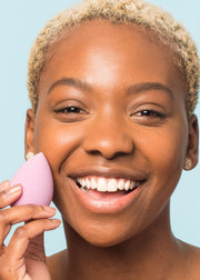 smiling girl holding a purple makeup blending sponge next to her face