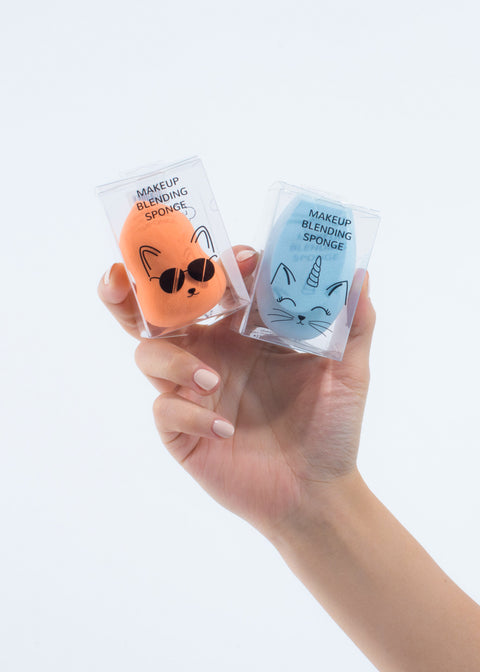 hand holding two makeup blending sponges, one orange and one blue