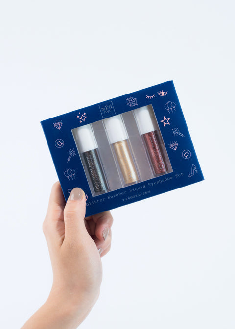hand holding a blue box that includes three bottles of glitter eyeshadow in gold, red and black