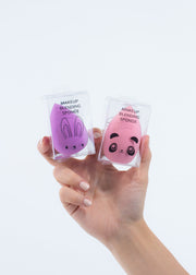 hand holding two makeup blending sponges, one purple and one pink