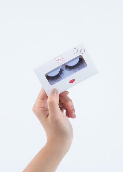 hand holding a pair of false eyelashes in a white box with red lips
