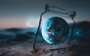 glass jar with world inside on a beach