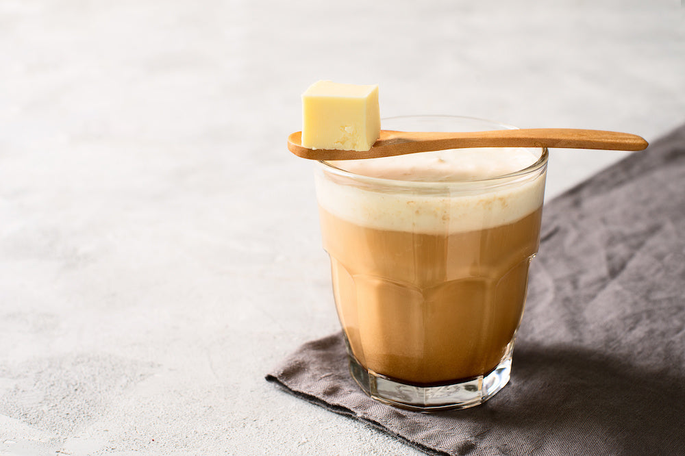 A glass of coffee with a wooden spoon on top containing a cube of butter