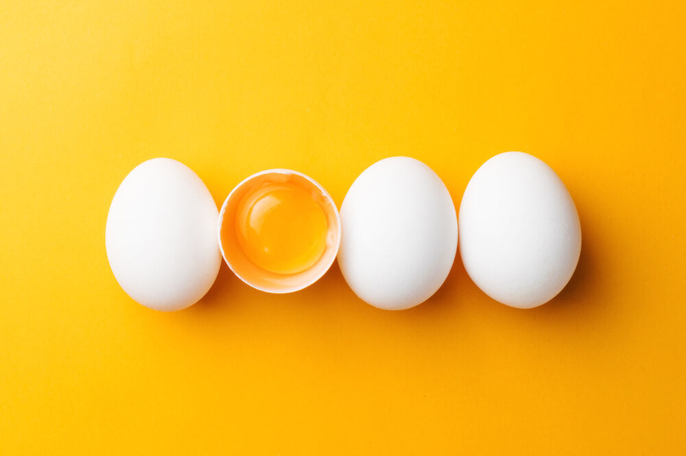 Egg yolk inside a cracked egg shell and three white eggs against a yellow orange background