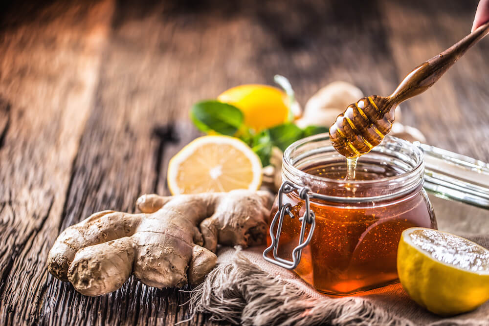 is honey paleo: a jar of honey with some ginger and lemon on a table