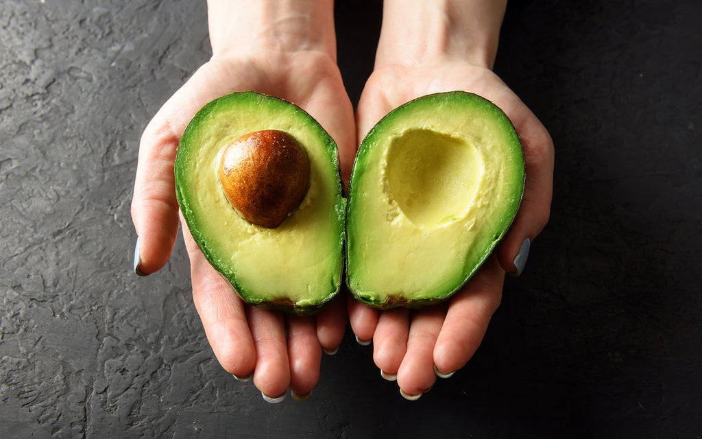 avocado oil: Woman's hands holding two halves of an avocado