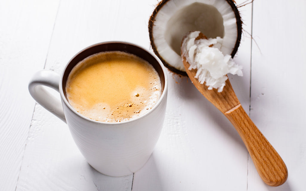 Cup of coffee with coconut and coconut oil on a wooden spoon