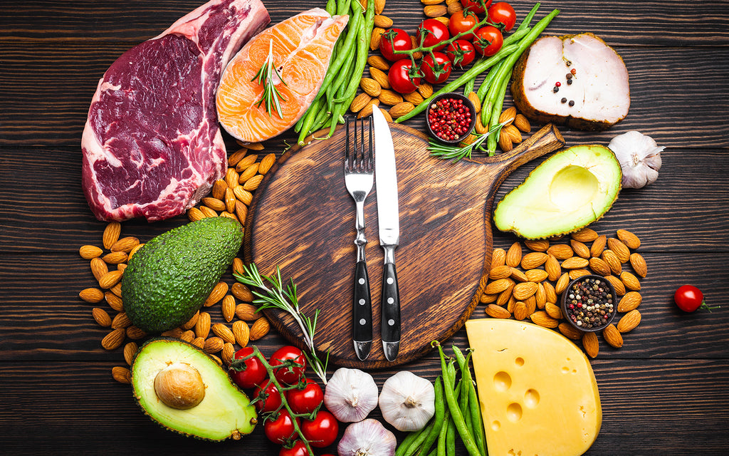 Keto diet for beginners: Variety of keto diet food with fork, knife and chopping board