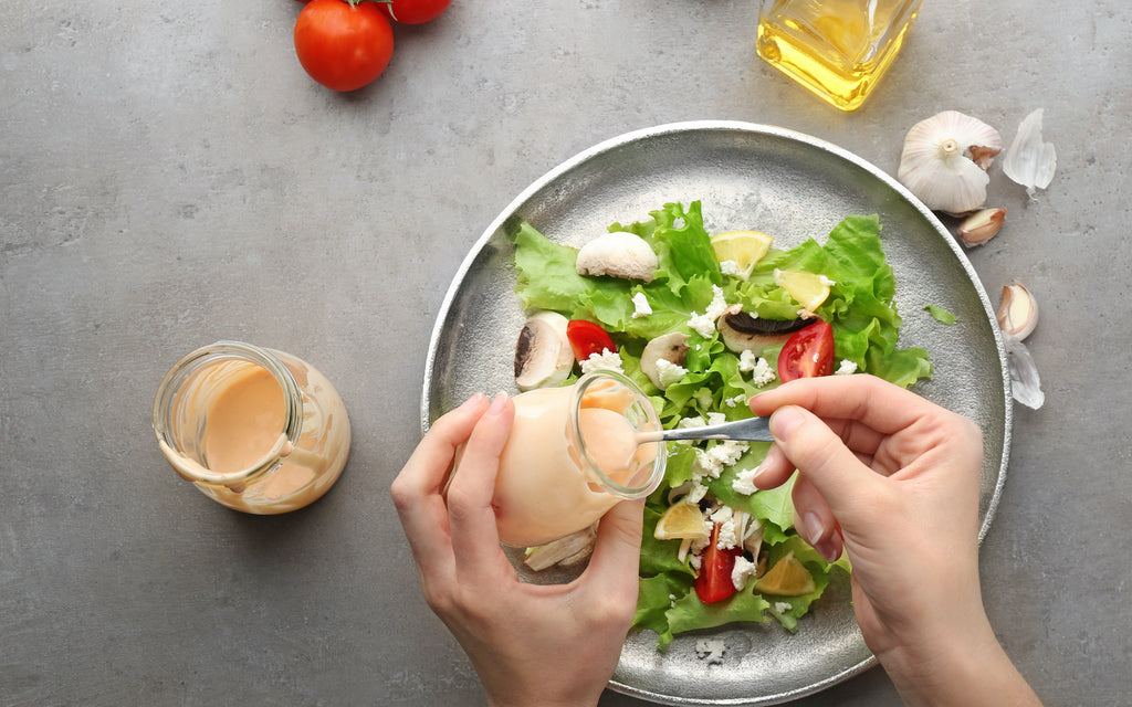 keto mayonnaise: Woman adding dressing to a fresh salad