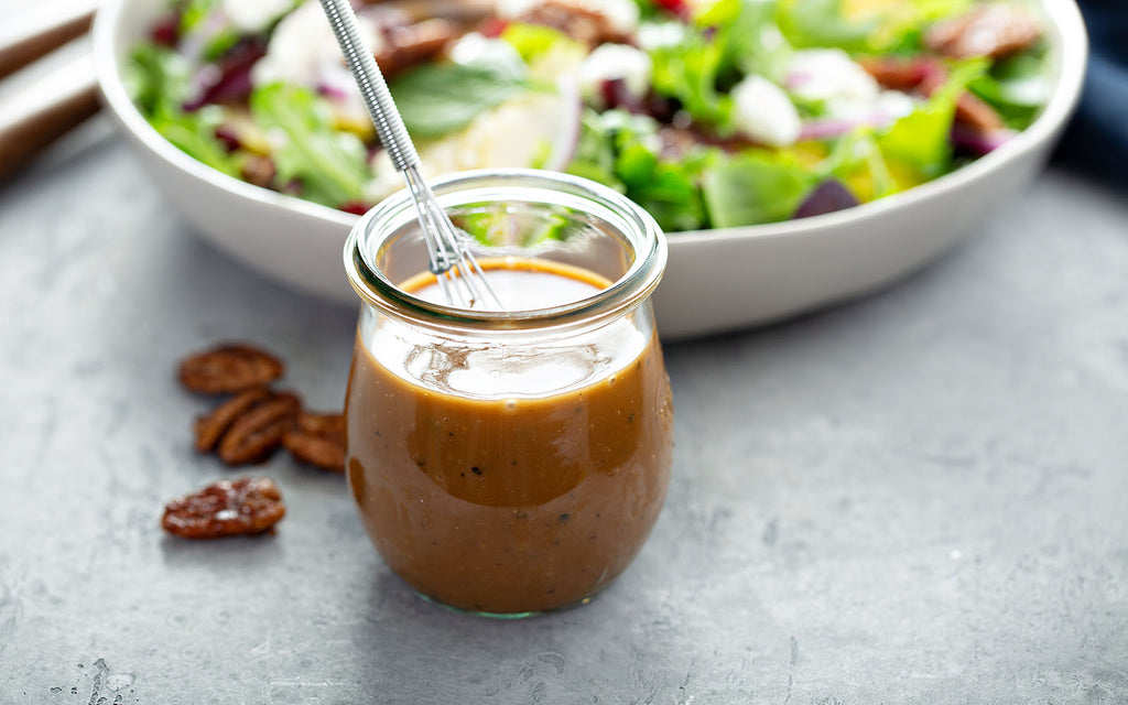 Salad dressing in a small glass jar with a whisk and a bowl of salad