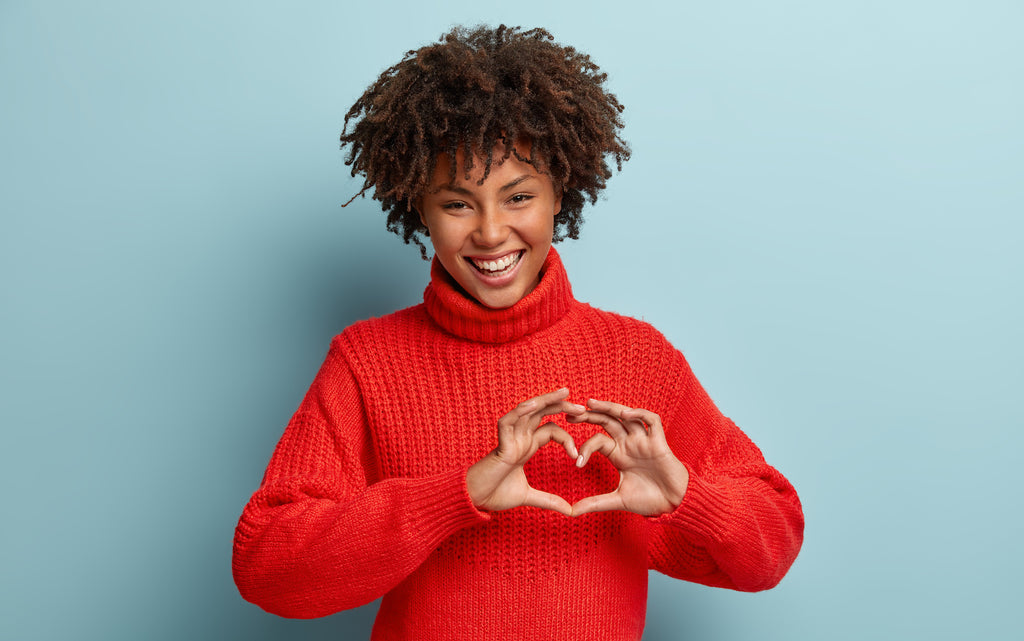B12 tablets: Smiling woman making a heart gesture with her hands