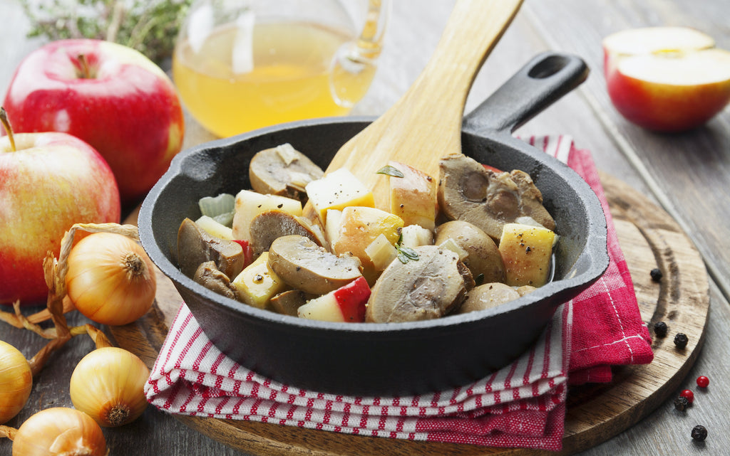 Kidney stew with apples on a cast iron pan surrounded by ingredients