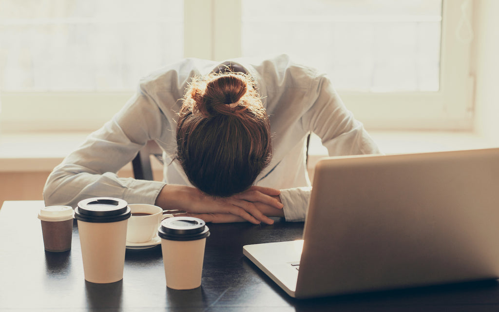Ketosis symptoms: Stressed woman slumping on the table with cups of coffee and laptop